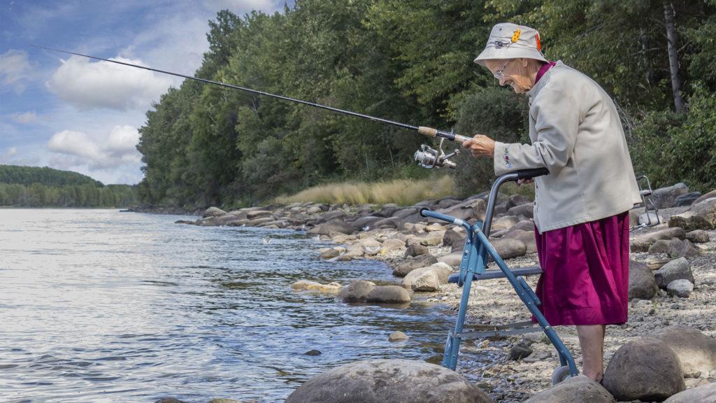 Wie Sie Ihre Mobilität erhalten - Ältere Frau mit Rollator am See beim Angeln